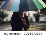 Stock photo  woman with colorful umbrella standing lonely and thinking in the rain weather blur focus concept 1011473989