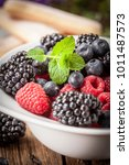 mix of berries in a bowl.... | Shutterstock . vector #1011487573