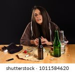 Small photo of Woman alcoholism social problem. Female drinking is cause of nervous stress. She in hood with rroup of green alcohol bottle in bad mood. Mess on table. Depression after break with guy.