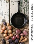 Small photo of Variety of raw uncooked organic potatoes different kind and colors red, yellow, purple on sackcloth with empty cast-iron pan over old white wooden background. Top view, space. Rustic style