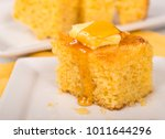 Stock photo piece of freshly baked cornbread with butter and honey dripping off the top 1011644296