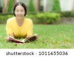 student reading a book in park | Shutterstock . vector #1011655036