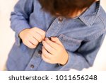 Small photo of Kid button blue jean.Kid try to button up jean shirt by himself. Kid fasten the buttons .Soft focus. Blur