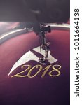 Small photo of Embroidery with embroidery machine of dog head and number 2018 in silver and gold on claret fabric - chinese new year concept - front view in portrait orientation and bright luxurious light mood