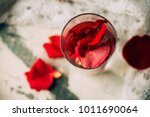 Stock photo glass delicious refreshing drink of rose petal flower on blue wooden background infusioned water 1011690064