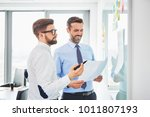 two coworkers discussing... | Shutterstock . vector #1011807193