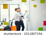 two creative workers in office... | Shutterstock . vector #1011807196