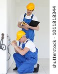 two builders working with... | Shutterstock . vector #1011818344
