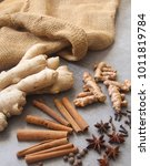 Small photo of a Beautiful Display of Spices Cinnamon sticks, Allspice, Star Anise, Cloves , Fresh Ginger and Turmeric root on a grey background