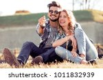 young couple sitting on grass... | Shutterstock . vector #1011832939