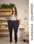 Small photo of Beautiful thin girl standing in big seize pants. looking funny.