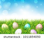 colorful easter eggs in grass.... | Shutterstock .eps vector #1011854050