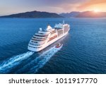 Cruise ship at harbor. Aerial view of beautiful large white ship at sunset. Colorful landscape with boats in marina bay, sea, colorful sky. Top view from drone of yacht. Luxury cruise. Floating liner - stock photo