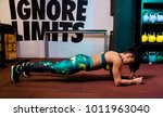 Small photo of Attractive female doing plank exercise in gym