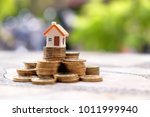 coin stacks and house model on... | Shutterstock . vector #1011999940
