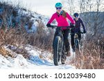 women mountain biking on fat... | Shutterstock . vector #1012039480