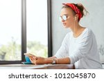 teenage hipster girl relaxes at ... | Shutterstock . vector #1012045870