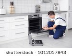 young man repairing oven in... | Shutterstock . vector #1012057843