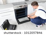 young man repairing oven in... | Shutterstock . vector #1012057846