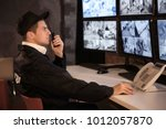 male security guard using radio ... | Shutterstock . vector #1012057870