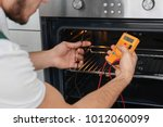 young man with multimeter... | Shutterstock . vector #1012060099