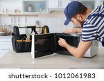young man repairing microwave... | Shutterstock . vector #1012061983