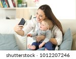 mother taking a selfie with her ... | Shutterstock . vector #1012207246