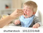 Small photo of Close up of a mother hand feeding his son who is crying sitting on a high chair