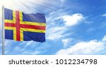 Small photo of Flag of Aland on flagpole against the blue sky