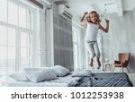 little cute girl is jumping on... | Shutterstock . vector #1012253938