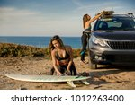 two beautiful surfer girls near ... | Shutterstock . vector #1012263400
