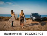 two beautiful surfer girls near ... | Shutterstock . vector #1012263403