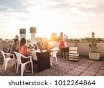 Small photo of Trendy friends having barbecue party on top of the roof - Happy people doing bbq dinner outdoor - Main focus on woman with yellow t-shirt - Fun, summer, city lifestyle and friendship concept
