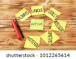 "Small photo of Stickers with abbreviation expansion for word ""Autism"" on wooden background"