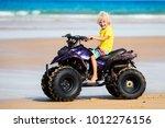 little boy riding quad bike on...   Shutterstock . vector #1012276156