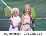 boy and girl playing tennis on... | Shutterstock . vector #1012281118