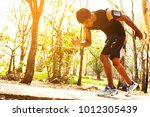 handsome man doing exercises... | Shutterstock . vector #1012305439