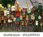 Stock photo many different shapes bird feeders birdhouse for nesting box hanging on wooden fence bird feeders 1012305910