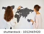 two women assemble cardboard... | Shutterstock . vector #1012465420