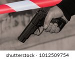 Small photo of A man's hand with a gun against the background of a restrictive tape of red and white color. A discriminatory concept. Toned.