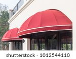 Small photo of red awning over door and concrete wall background, free copy space for text