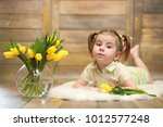 a small child with a bouquet of ... | Shutterstock . vector #1012577248