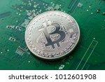 silver bitcoin on green chipset.... | Shutterstock . vector #1012601908