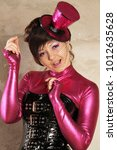 Small photo of beautiful woman stands in a crimson fetish overalls, black shiny bdsm corset with buckles, burlesque tutu skirt and cute pinup hat with a veil