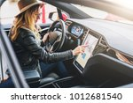 young woman sits behind wheel... | Shutterstock . vector #1012681540