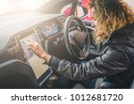 young woman sits behind wheel... | Shutterstock . vector #1012681720