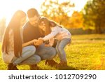 family playing in autumn park... | Shutterstock . vector #1012709290