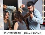 male hairdresser cutting hair ... | Shutterstock . vector #1012716424