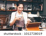 barista woman using digital... | Shutterstock . vector #1012728019