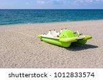 Green Pedalo On A Gravel Beach...